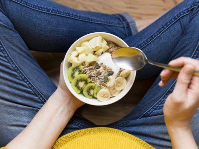 Eating healthy breakfast bowl. Yogurt, buckwheat, seeds, fresh fruits in white bowl in woman' s hands. Clean eating, dieting, detox, vegetarian food concept