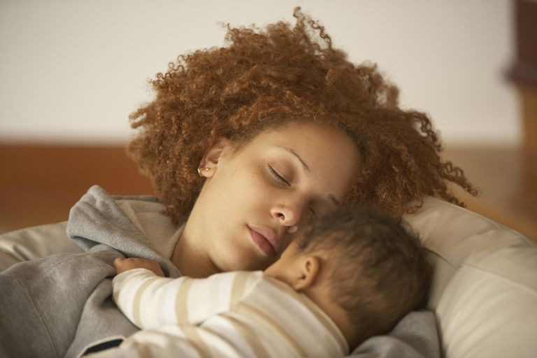 African American woman sleeping with her baby