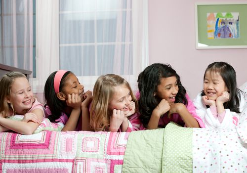 Five young girls on a bed having a sleepover
