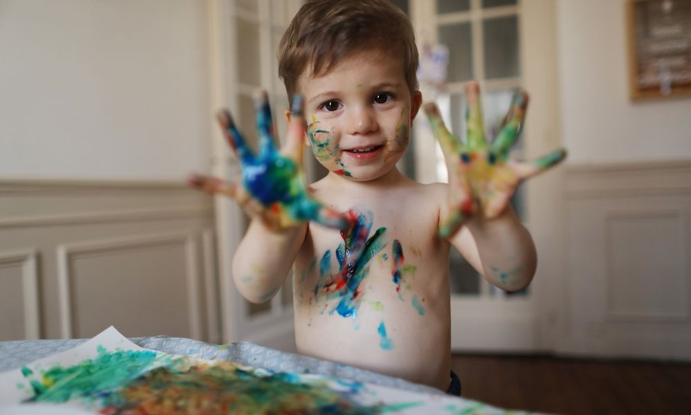 little boy using finger paints