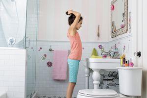 Tween girl doing her hair in the bathroom mirror