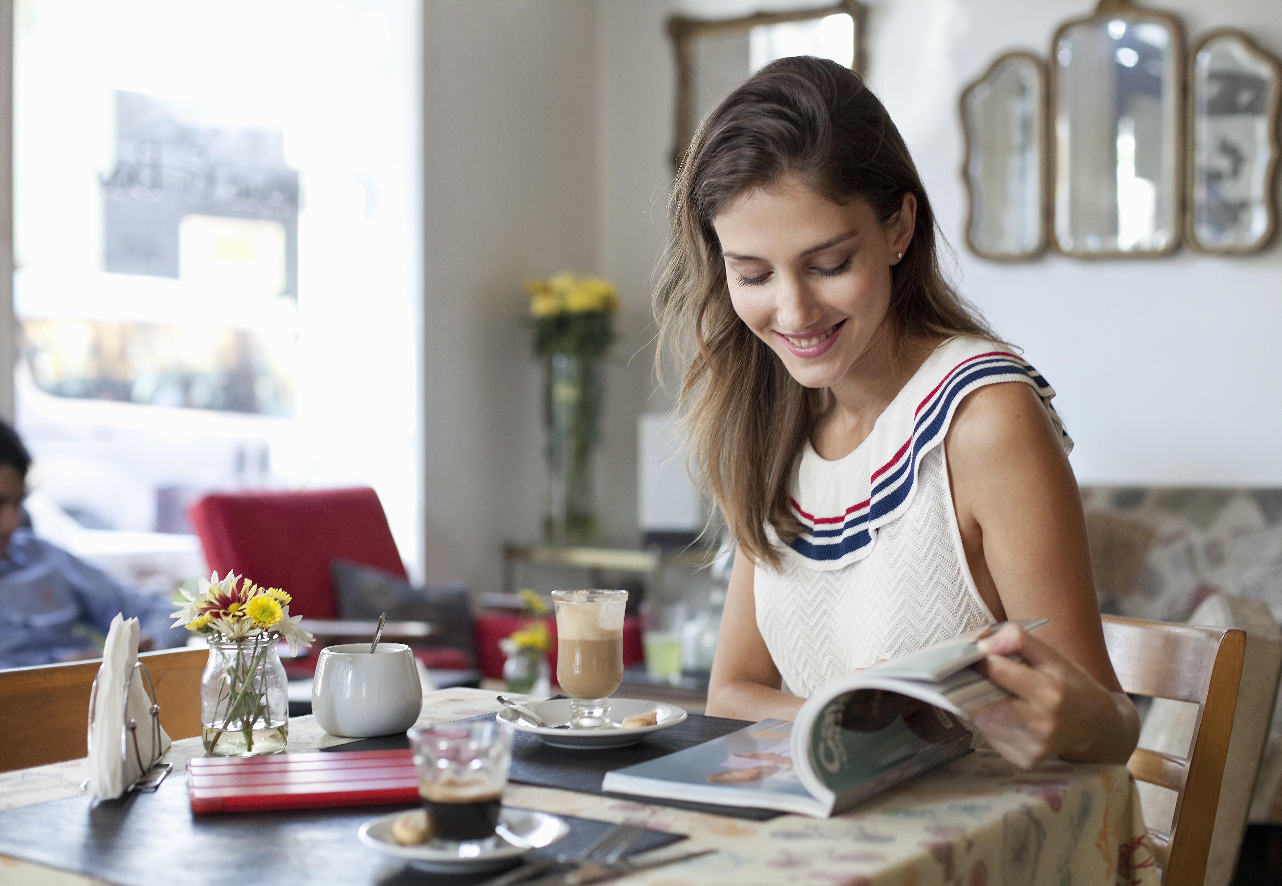 woman in café, having coffee, looking at magazine