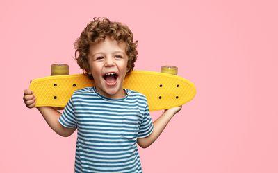 Cute boy holding a yellow skateboard