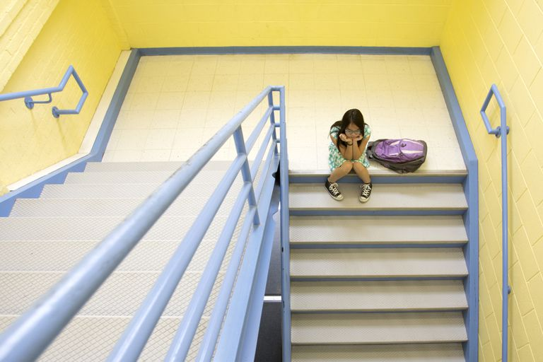 Bullied girl sitting on steps at school