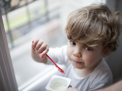 Toddler boy eating yogurt, portrait