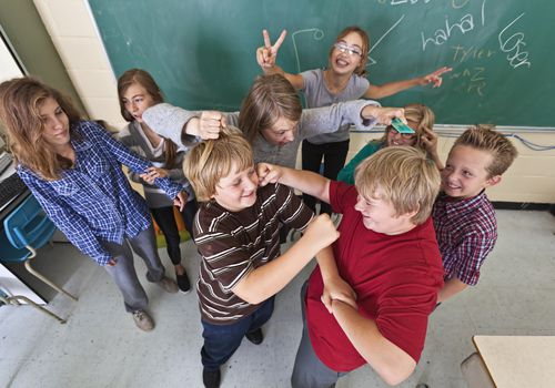 group of middle school kids rough-housing in classroom