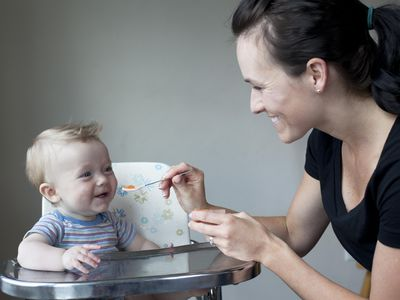 Young mother feeding her baby boy in high chair.