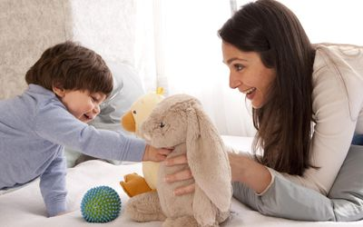 Mom and toddler boy playing with stuffed animals.