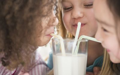 Girls sharing glass of milk