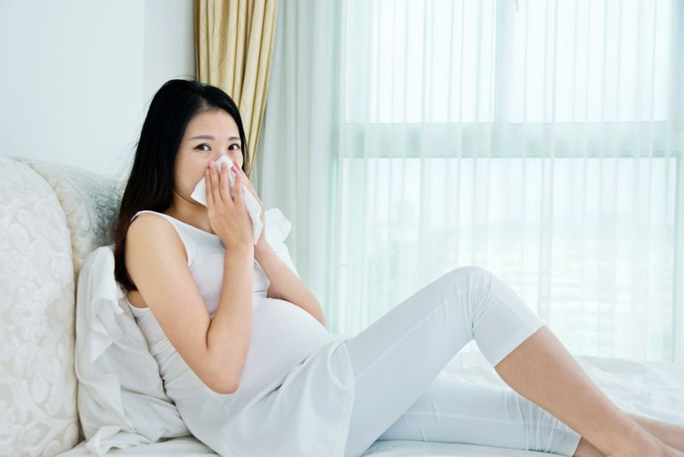 Pregnant women blowing her nose in bed