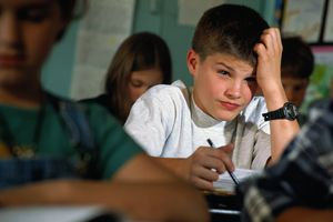 Young student (8-10) sitting at desk with pensive expression