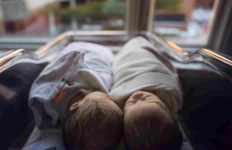 Newborn twins sleeping together in bassinet