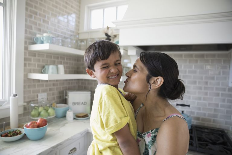 Playful mother kissing laughing son in kitchen