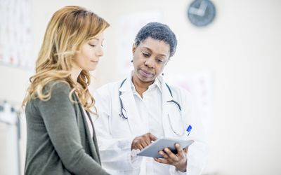 woman and female doctor looking at tablet in office