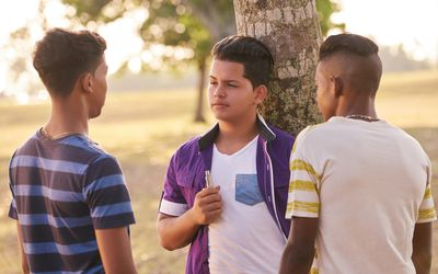 three teen boys discussing vaping