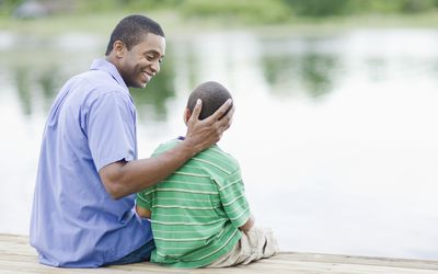 Dad and son sitting by a lake.
