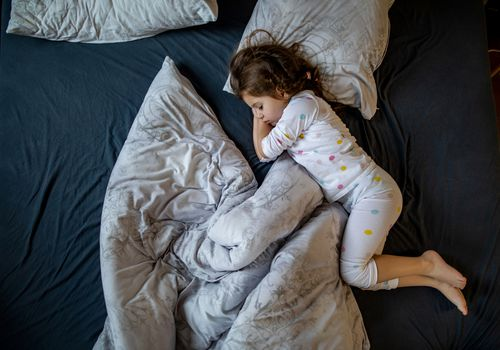 A little girl sleeping in a bed with blanket and pillows askew