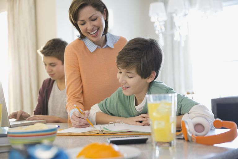Smiling woman assisting son with homework