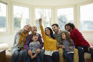 Multi generation family on window seat using smartphone to take selfie