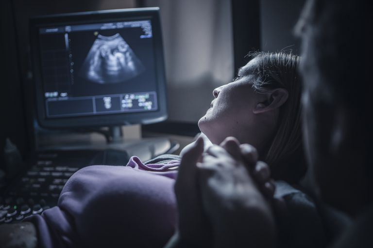 Woman and her partner looking at ultrasound machine, looking for signs of clinical pregnancy