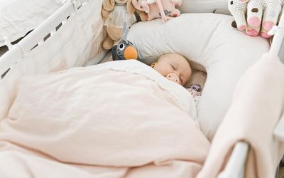 e5c6981671 Danish baby girl sleeping in crib with bumper