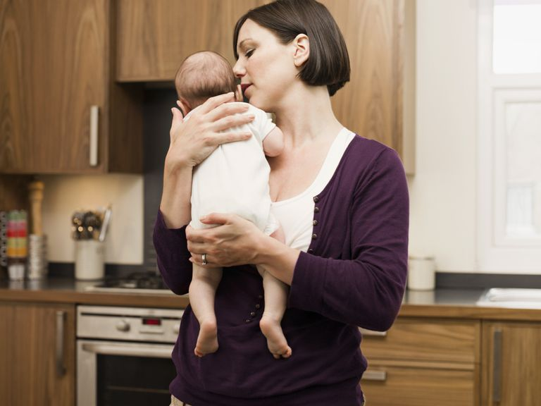 mother burping baby over shoulder in kitchen
