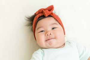 Baby girl with burnt orange headband and mint onesie looking at camera