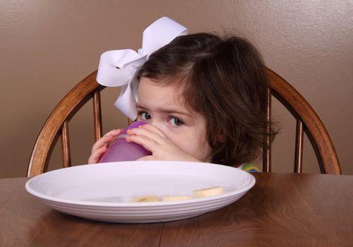 child drinking juice and eating banana