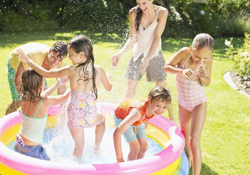 Family playing outdoors in a blow-up kiddie pool