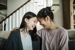 Mother and teenage daughter smiling and talking at home