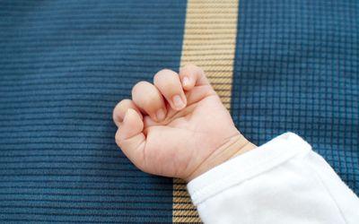 A newborn hand on blue background
