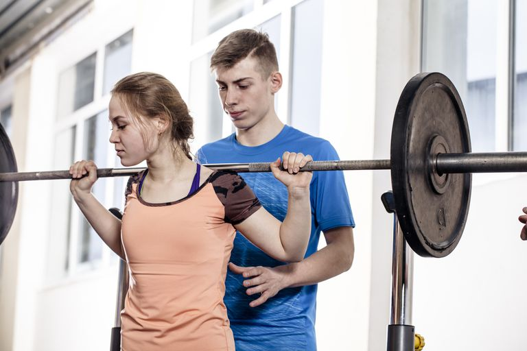 Youth powerlifting - teen girl lifting barbell