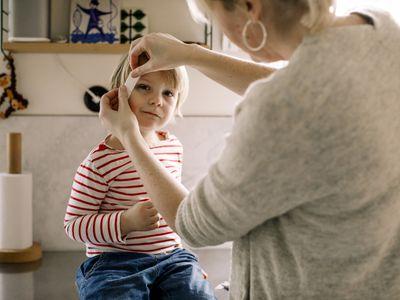 mom putting bandaid on a little boy's head