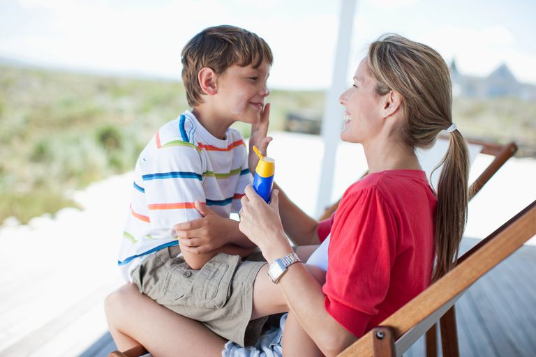 A mother applying sunscreen on her son.