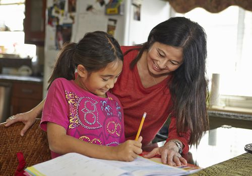 Mother and tween daughter working on homework at kitchen table