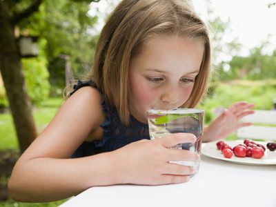 girl drinking water at a table outdoors