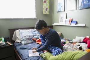 Boy in pajamas drawing with digital tablet on bed