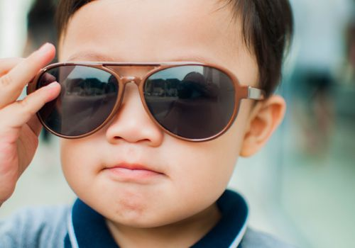 dark-haired toddler wearing oversized sunglasses