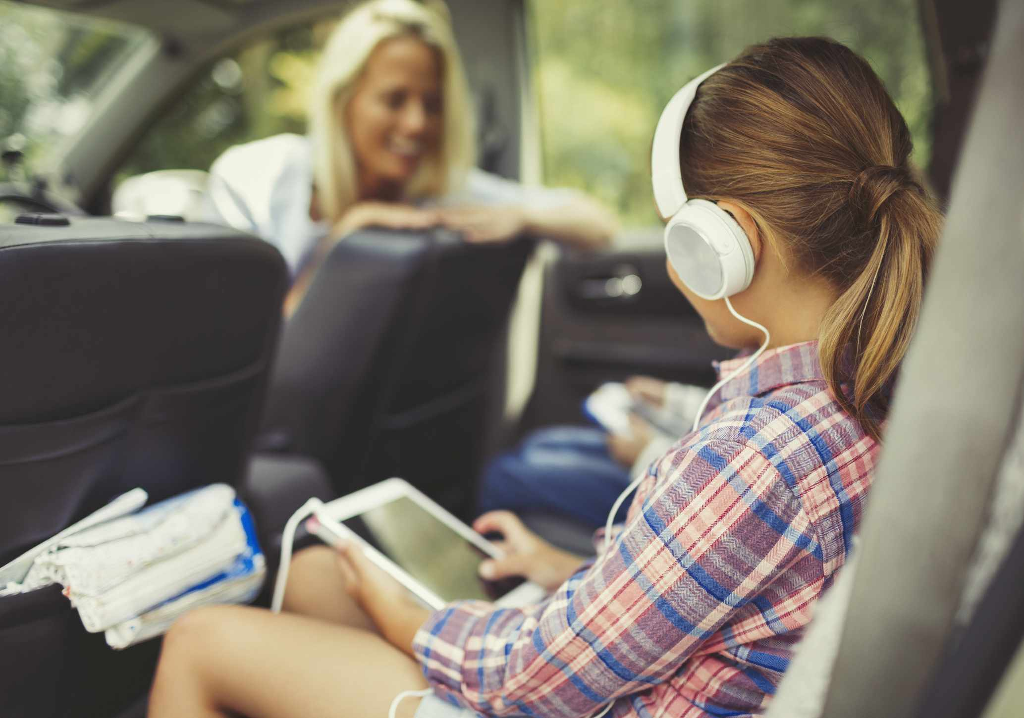 Girl listening to headphones in a car.