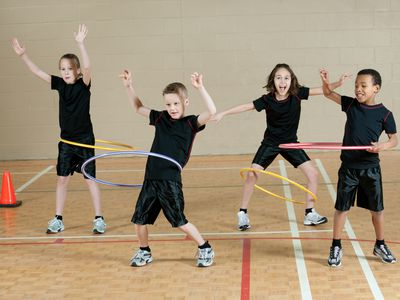 Kids in school gym playing with hula hoops