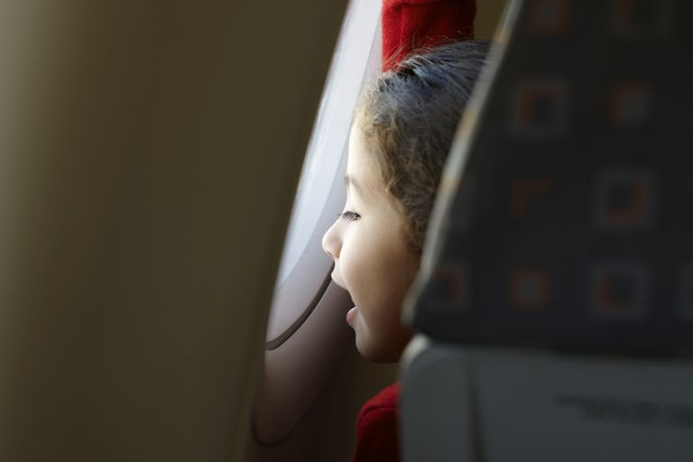 Young child looking through airplane window