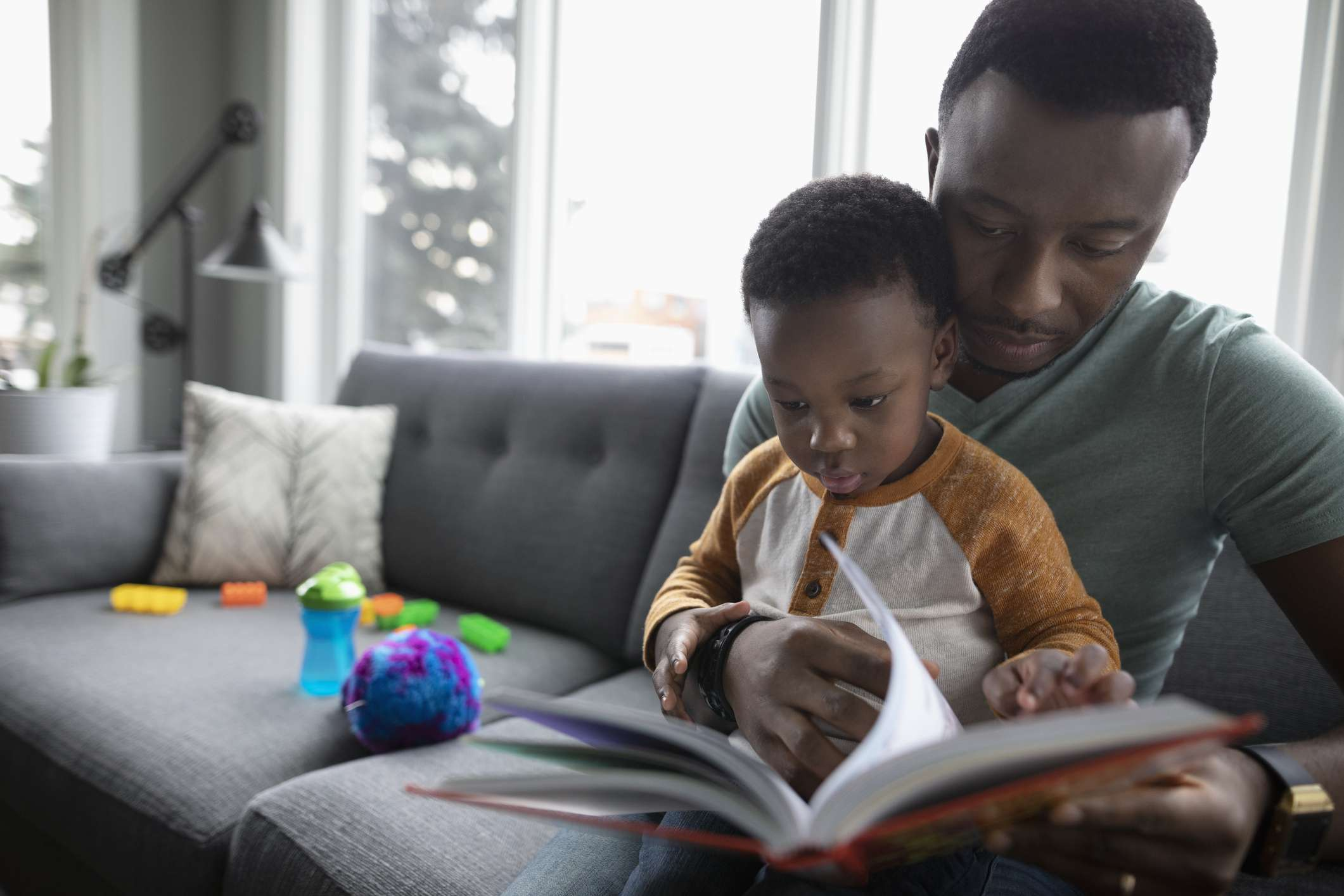 Father and toddler son reading book on living room sofa