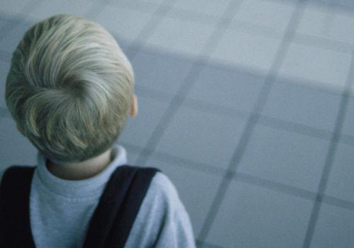 Back of boy's head in in empty room