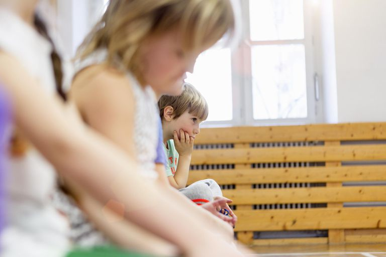 Children sitting on bench in school hall, looking sad