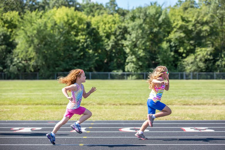 Two Young Girls Running On Outdoor Track