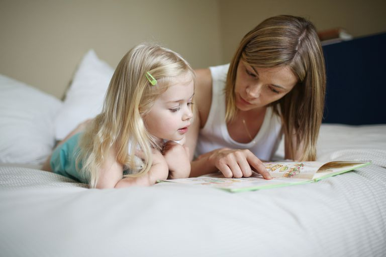 Mother and young daughter reading on a bed
