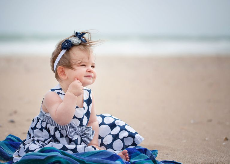 Cute baby girl sitting on the beach