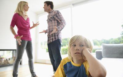 Boy looking away as parents argue behind him