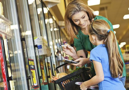 Little girl helping mom shop at supermarket with grocery list