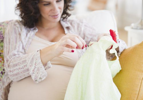 Pregnant woman sewing button on baby clothes